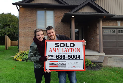 A couple standing outside of their newly sold home